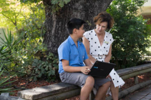 St Raphael South Hurstville Principal sitting on bench with student looking at laptop